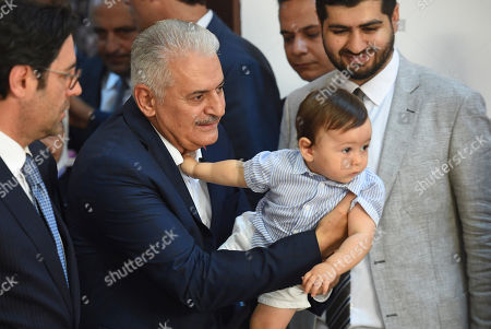 Turkish ruling party Justice and Development Party (AKP) candidate for Istanbul Mayor Binali Yildirim (C) holding his grandson arrives to cast his vote in the the Istanbul mayoral elections re-run, in Istanbul, Turkey, 23 June 2019. Some 10.5 million people will vote on the day in a re-run of the mayoral election. The Turkish Electoral Commission ordered a repeat of the mayoral election in Istanbul for 23 June 2019, after Turkish President Erdogan's AK Party had alleged there was 'corruption' behind his party losing in the 31 March 2019 polls.