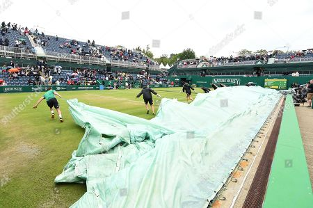 Rain covers are pulled across the Ann Jones Centre Court during the Womens doubles final between Anna-Lena Groenefeld of Germany and Demi Schuurs of the Netherlands against Su-Wei Hsieh of Chinese Taipei and Barbora Strycova of the Czech Republic.