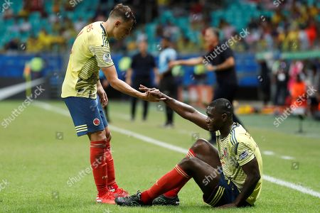 Colombia's Santiago Arias (L) helps teammate Cristian Zapata (R) during the Copa America 2019 Group B soccer match between Colombia and Paraguay, at Arena Fonte Nova Stadium in Salvador, Brazil, 23 June 2019.