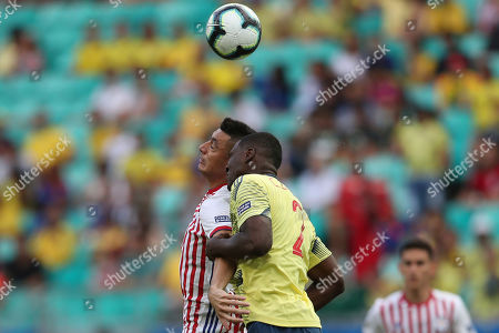 Paraguay's Oscar Cardozo, left, and Colombia's Cristian Zapata jump for a header during a Copa America Group B soccer match at the Arena Fonte Nova in Salvador, Brazil