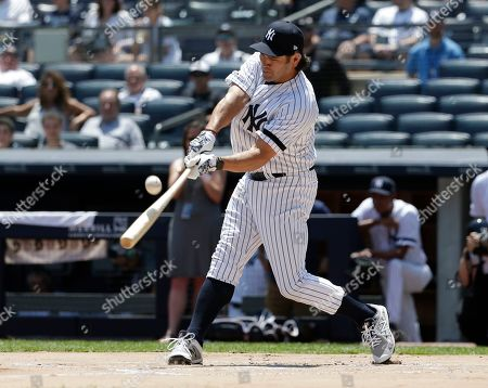 Former New York Yankee Johnny Damon swings at the ball during Old Timer's Day at Yankee Stadium, in New York