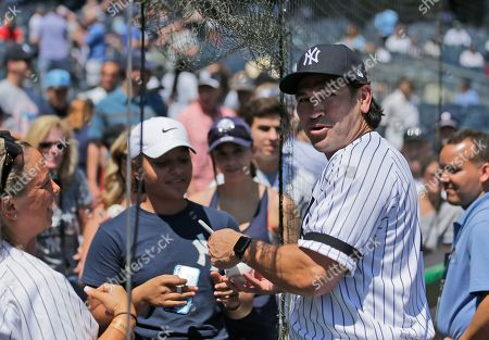 Former New York Yankee Johnny Damon sign autographs during Old Timer's Day at Yankee Stadium, in New York
