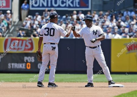 Former New York Yankee Homer Bush, right, celebrates his double with Willie Randolph during Old Timer's Day at Yankee Stadium, in New York