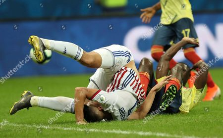 Oscar Cardozo, Cristian Zapata. Paraguay's Oscar Cardozo, left, and Colombia's Cristian Zapata fall after fighting for the ball during a Copa America Group B soccer match at the Arena Fonte Nova in Salvador, Brazil