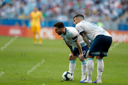 Argentina's Lionel Messi, left, and teammates Leandro Paredes plan a free kick against Qatar during a Copa America Group B soccer match at Arena do Gremio, Porto Alegre, Brazil