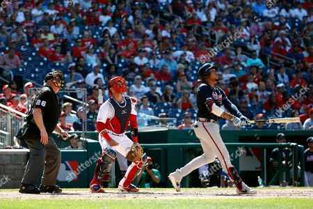 Johan Camargo, Yan Gomes, Bill Miller. Atlanta Braves' Johan Camargo, right, watches his two-run home run in front of Washington Nationals catcher Yan Gomes and umpire Bill Miller in the 10th inning of a baseball game, in Washington. Atlanta won 4-3 in 10 innings