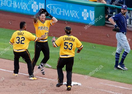 San Diego Padres first baseman Eric Hosmer, right, walks off the field as Pittsburgh Pirates' Kevin Newman (27) celebrates with Elias Diaz (32) and Melky Cabrera (53) after drawing a walk from San Diego Padres relief pitcher Matt Wisler with bases loaded, forcing in the walk-off game-winning run during the 11th inning of a baseball game in Pittsburgh, . The Pirates won in 11-innings, 11-10