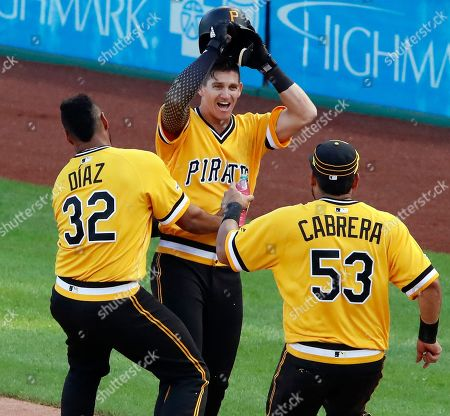 Pittsburgh Pirates' Kevin Newman, center, celebrates with Elias Diaz (32) and Melky Cabrera (53) after drawing a walk from San Diego Padres relief pitcher Matt Wisler with bases loaded, forcing in the walk-off game-winning run during the 11th inning of a baseball game in Pittsburgh, . The Pirates won in 11-innings, 11-10