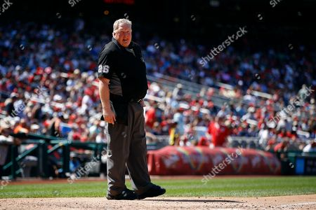 Umpire Bill Miller stands behind home plate during a baseball game between the Atlanta Braves and the Washington Nationals, in Washington