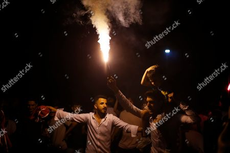 Supporters of Ekrem Imamoglu, the candidate of the secular opposition Republican People's Party, CHP, light up a flare as they celebrate in Istanbul, . Imamoglu declared victory in the Istanbul mayor's race for a second time Sunday after Binali Yildirim, the government-backed candidate conceded defeat in a high-stakes repeat election