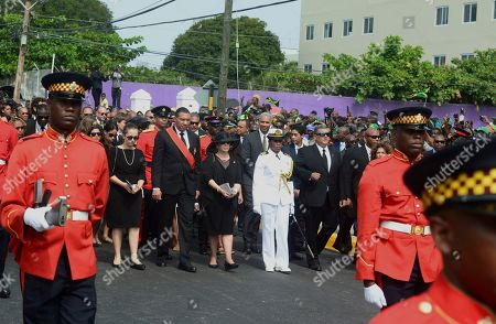 Prime Minister of Jamaica Andrew Holness, center wearing a red sash, is flanked by his wife Carla Seaga, right, and daughter Gabrielle Seaga, as they walk behind the casket of former Jamaican Prime Minister Edward Seaga during his funeral procession in Kingston, Jamaica, . Seaga served as prime minister from 1980 until 1989 and was the only remaining member of the generation of leaders who drafted the constitution when the island gained independence from Britain in 1962. He died in Florida on May 28 on his 89th birthday