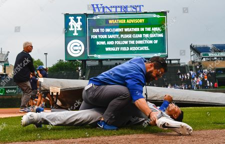 New York Mets right fielder Carlos Gomez (91) stretches with a trainer before a baseball game against the Chicago Cubs, in Chicago. Rain delayed the game breifly