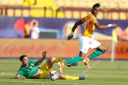 South Africa's Dean Furman, left, scleras the ball ahed of Ivory Coast's Jonathan Kodjia during the African Cup of Nations group D soccer match between Ivory Coast and South Africa in Al Salam Stadium in Cairo, Egypt, . Ivory Coast won 1-0