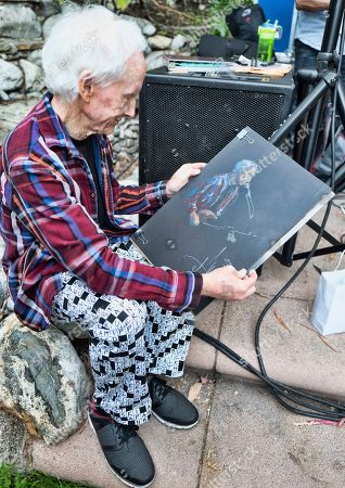 Stock Image of American guitarist and singer-songwriter best known as the guitarist of the rock band The Doors, Robbie Krieger looks at a sketch of himself after a performance in Los Angeles