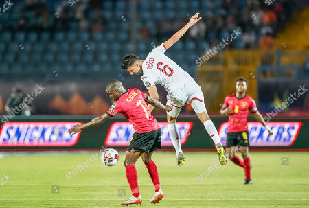 Rami Bedoui of Tunisia and Djalma Braune Manuel Abel Campos of Angola challenging for the ball during the African Cup of Nations match between Tunisia and Angola at the Suez Army stadium in Suez, Egypt