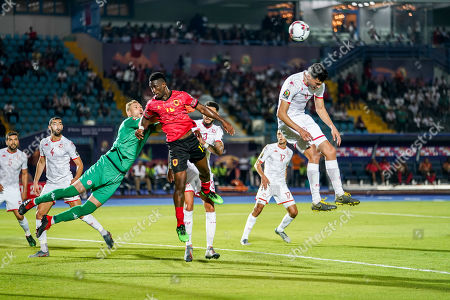 Stock Picture of Farouk Ben Mustapha of Tunisia boxing the ball in front of Bartolomeu Jacinto Quissanga Quissanga of Angola during the African Cup of Nations match between Tunisia and Angola at the Suez Army stadium in Suez, Egypt