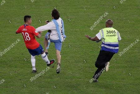 Stock Photo of Chile's Gonzalo Jara, left, tries to stop an Uruguay soccer fan who entered the pitch during a Copa America Group C soccer match at Maracana stadium in Rio de Janeiro, Brazil