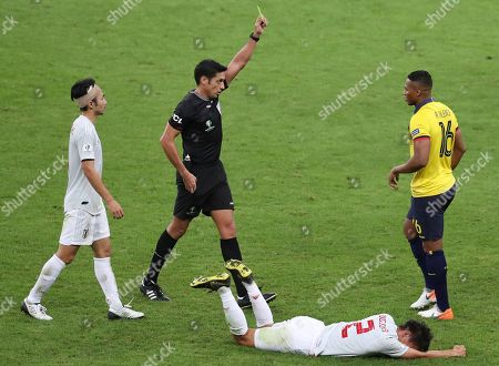Referee Jesus Valenzuela awards a yellow card to Ecuador's Antonio Valencia after he fouled Japan's Daiki Sugioka, down, during a Copa America Group C soccer match at the Mineirao stadium in Belo Horizonte, Brazil