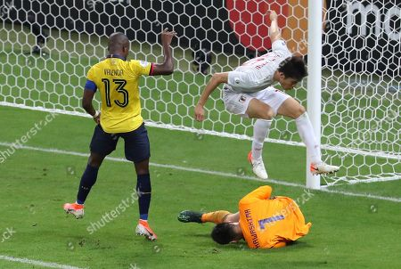 Japan's goalkeeper Eiji Kawashima stops the ball as teammate Takehiro Tomiyasu jumps over him, while Ecuador's Enner Valencia looks on during a Copa America Group C soccer match at the Mineirao stadium in Belo Horizonte, Brazil