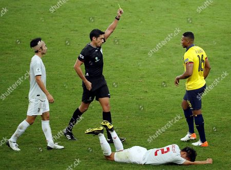 Antonio Valencia (R) of Ecuador receives a yellow card for fouling Daiki Suga (bottom) of Japan during the Copa America 2019 Group C soccer match between Ecuador and Japan, at Mineirao Stadium in Belo Horizonte, Brazil, 24 June 2019.