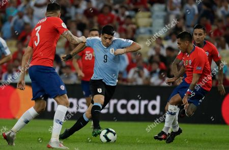 Uruguay's Luis Suarez, center, is challenged by Chile's Guillermo Maripan, left, and Gonzalo Jara during a Copa America Group C soccer match at the Maracana stadium in Rio de Janeiro, Brazil