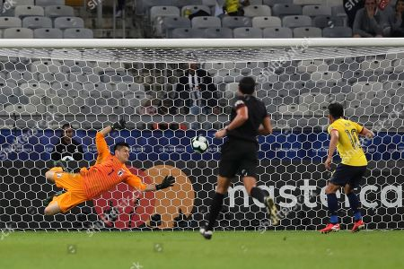 Ecuador's Angel Mena, right, scores his side's first goal past Japan's goalkeeper Eiji Kawashima, left, during a Copa America Group C soccer match at the Mineirao stadium in Belo Horizonte, Brazil
