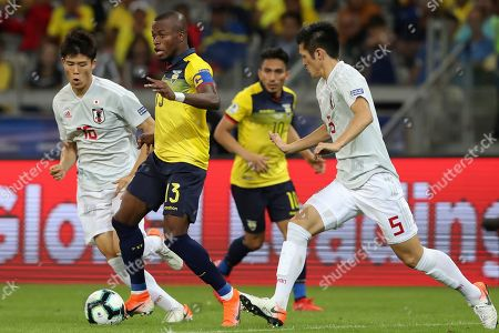 Ecuador's Enner Valencia, second left, drives the ball past Japan's Naomichi Ueda, right, during a Copa America Group C soccer match at the Mineirao stadium in Belo Horizonte, Brazil