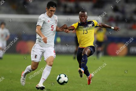 Japan's Naomichi Ueda, left, vies for the ball with Ecuador's Enner Valencia during a Copa America Group C soccer match at the Mineirao stadium in Belo Horizonte, Brazil
