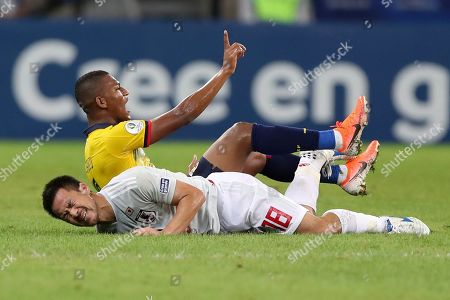 Japan's Shinji Okazaki, bottom, reacts after colliding with Ecuador's Carlos Gruezo during a Copa America Group C soccer match at the Mineirao stadium in Belo Horizonte, Brazil