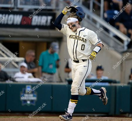 Michigan catcher Joe Donovan (0) celebrates after hitting a home run against Vanderbilt during the eighth inning in Game 1 of the NCAA College World Series baseball finals in Omaha, Neb