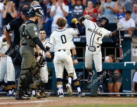 Michigan's Joe Donovan (0) celebrates with teammate Ako Thomas (4) after his home run against Vanderbilt during the eighth inning in Game 1 of the NCAA College World Series baseball finals in Omaha, Neb