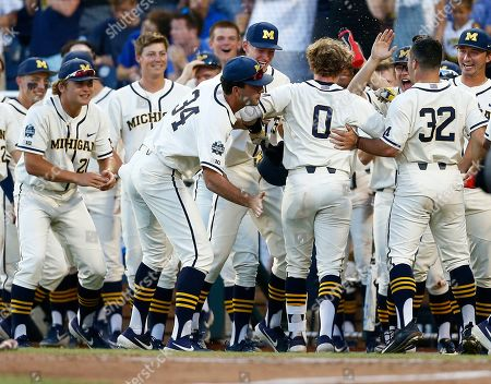 Michigan's Joe Donovan (0) celebrates with teammates after his home run against Vanderbilt during the eighth inning in Game 1 of the NCAA College World Series baseball finals in Omaha, Neb