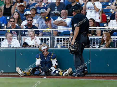 Michigan catcher Joe Donovan reacts after missing a pop fly by Vanderbilt during the second inning in Game 1 of the NCAA College World Series baseball finals in Omaha, Neb