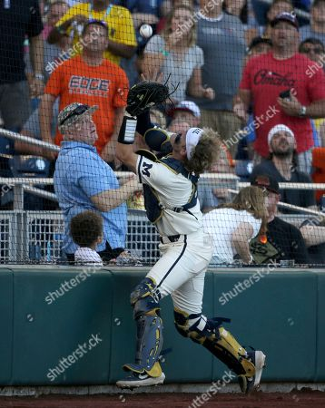Michigan catcher Joe Donovan catches a foul ball against Vanderbilt during the third inning in Game 1 of the NCAA College World Series baseball finals in Omaha, Neb