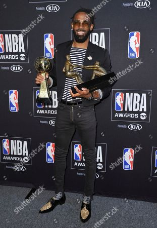 NBA player Mike Conley Jr., of the Memphis Grizzlies, poses in the press room with the NBA teammate award and sportsmanship of the year award at the NBA Awards, at the Barker Hangar in Santa Monica, Calif