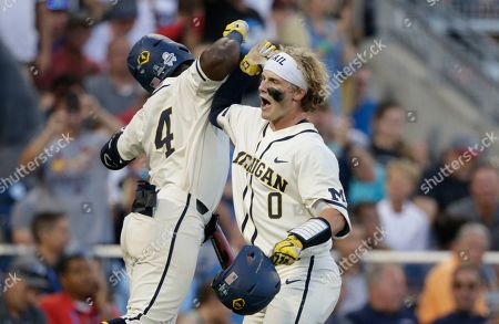Michigan's Joe Donovan (0) celebrates with Ako Thomas (4) after hitting a home run against Vanderbilt during the eighth inning in Game 1 of the NCAA College World Series baseball finals in Omaha, Neb