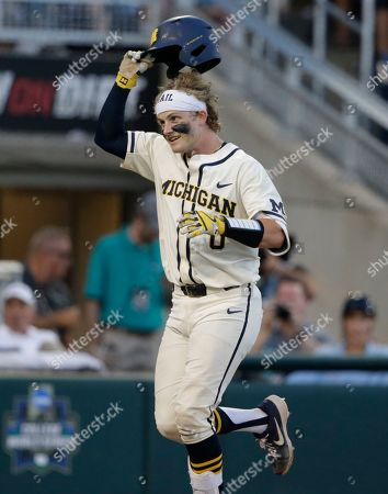 Stock Photo of Michigan's Joe Donovan (0) celebrates after hitting a home run against Vanderbilt during the eighth inning in Game 1 of the NCAA College World Series baseball finals in Omaha, Neb