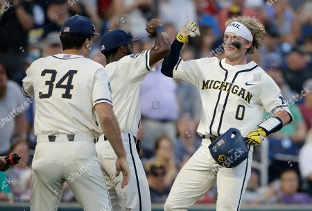 Michigan's Joe Donovan (0) celebrates with teammates after hitting a home run against Vanderbilt during the eighth inning in Game 1 of the NCAA College World Series baseball finals in Omaha, Neb