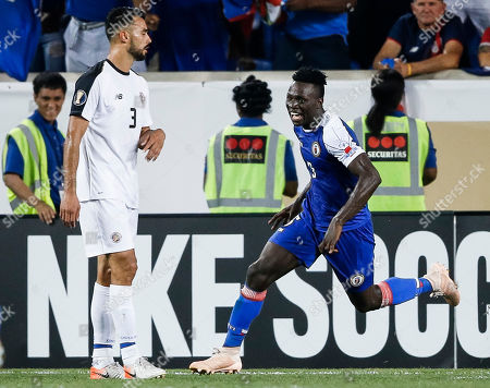 Haiti's Djimy Alexis (R) celebrates scoring a goal as he runs past Costa Rica's Giancarlo Gonzalez (L) during the second half of the CONCACAF Gold Cup group stage soccer match between Haiti and Costa Rica at Red Bull Stadium in Harrison, New Jersey, USA, 24 June 2019.