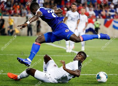 Haiti's Alex Junior Christian (top) and Costa Rica's Joel Campbell (bottom) fight for the ball during the first half of the CONCACAF Gold Cup group stage soccer match between Haiti and Costa Rica at Red Bull Stadium in Harrison, New Jersey, USA, 24 June 2019.