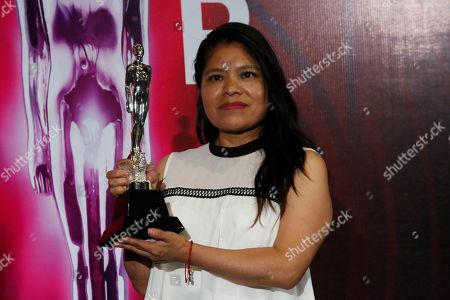 "Mexican activist and domestic worker Marcelina Bautista poses with Alfonso Cuaron's Ariel Award for Best Director for ""Roma"" after accepting it in his name, during the 61st edition of the Ariel Awards from the Mexican Academy of Arts and Cinematographic Sciences at the National Cineteca in Mexico City"