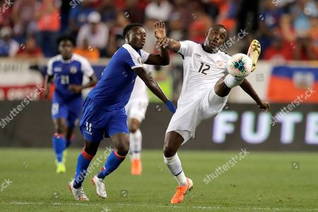 Costa Rica forward Joel Campbell (12) tries to get a foot on the ball while challenged by Haiti midfielder Derrick Etienne during the first half of a CONCACAF Gold Cup soccer match, in Harrison, N.J