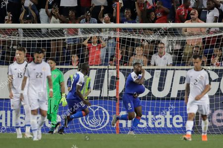Haiti forward Duckens Nazon, center, celebrates after scoring a penalty kick goal against Leonel Moreira during the second half of a CONCACAF Gold Cup soccer match, in Harrison, N.J