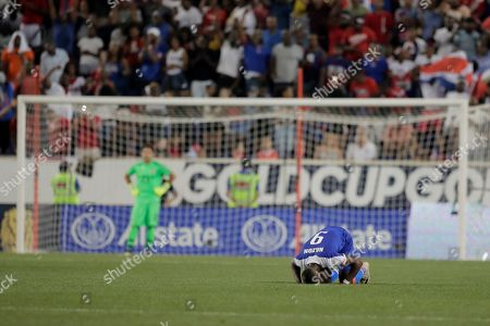 Haiti forward Duckens Nazon (9) kisses the turf after scoring a penalty kick goal against Costa Rica goalkeeper Leonel Moreira, back left, during the second half of a CONCACAF Gold Cup soccer match, in Harrison, N.J