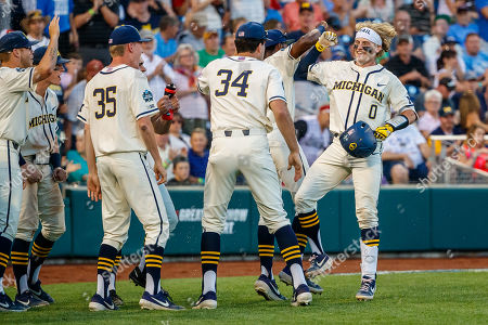 Omaha, NE U.S. - Michigan's Joe Donovan #0 is congratulated by teammates after his home run in action during game 1 of the NCAA Men's College World Series between Michigan Wolverines and Vanderbilt Commodores at the TD Ameritrade Park in Omaha, NE..Attendance: 24,707.Michigan won 7-3