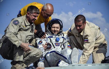 Ground personnel help Russian cosmonaut Oleg Kononenko (C) to get out of the Soyuz MS-11 capsule shortly after landing in a remote area outside the town of Dzhezkazgan (Zhezkazgan), Kazakhstan, 25 June 2019.