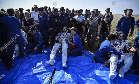 Russian cosmonaut Oleg Kononenko (C), NASA astronaut Anne McClain (R) and David Saint-Jacques of the Canadian Space Agency rest in chairs shortly after landing in a remote area outside the town of Dzhezkazgan (Zhezkazgan), Kazakhstan, 25 June 2019.  The Soyuz MS-11 capsule with the International Space Station (ISS) crew of NASA astronaut Anne McClain, Russian cosmonaut Oleg Kononenko and David Saint-Jacques of the Canadian Space Agency on board landed in the Kazakh steppe on 25 June 2019.