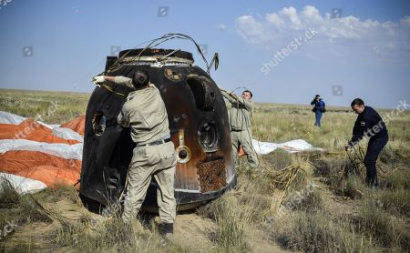 A search and rescue team works on the site of landing of the Soyuz MS-11 capsule carrying the International Space Station (ISS) crew of NASA astronaut Anne McClain, Russian cosmonaut Oleg Kononenko and David Saint-Jacques of the Canadian Space Agency, in a remote area outside the town of Dzhezkazgan (Zhezkazgan), Kazakhstan, 25 June  2019.
