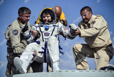 Ground personnel help NASA astronaut Anne McClain to get out of the Soyuz MS-11 capsule shortly after landing in a remote area outside the town of Dzhezkazgan (Zhezkazgan), Kazakhstan, 25 June  2019.  The Soyuz MS-11 capsule with the International Space Station (ISS) crew of NASA astronaut Anne McClain, Russian cosmonaut Oleg Kononenko and David Saint-Jacques of the Canadian Space Agency on board landed safly in the Kazakh steppe on 25 June 2019.