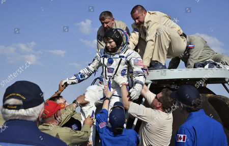 Ground personnel help NASA astronaut Anne McClain to get out of the Soyuz MS-11 capsule shortly after landing in a remote area outside the town of Dzhezkazgan (Zhezkazgan), Kazakhstan, 25 June  2019.  The Soyuz MS-11 capsule with the International Space Station (ISS) crew of NASA astronaut Anne McClain, Russian cosmonaut Oleg Kononenko and David Saint-Jacques of the Canadian Space Agency on board landed in the Kazakh steppe on 25 June 2019.